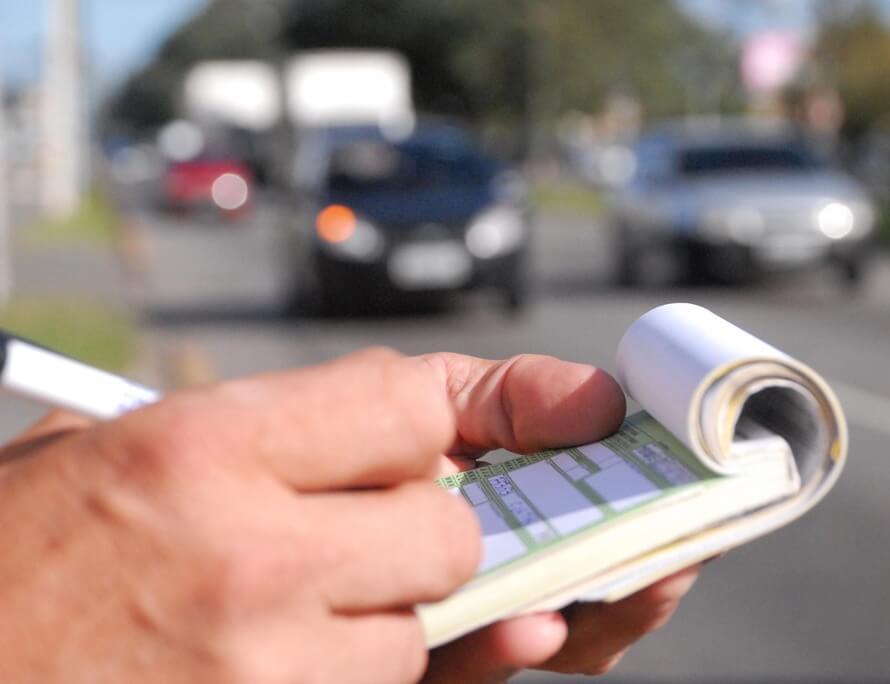 Guarda de trânsito anotando infração