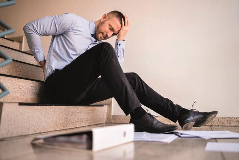 Imagem de um homem que teve uma queda em uma escada